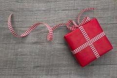 Geschenk eingewickelt im roten Papier auf einem hölzernen Hintergrund, kariertes Band Stockfotos