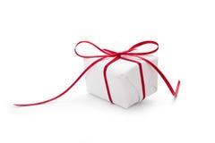 Geschenk eingewickelt im Weißbuch und mit rotem Band gebunden Lizenzfreies Stockfoto