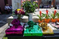 Geschenk im Glanzpapier und Blumensträuße auf der Tabelle im Freien stockbild