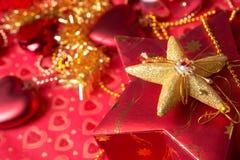 Geschenk im Kasten mit Herzdekoration am roten Hintergrund Lizenzfreie Stockfotografie
