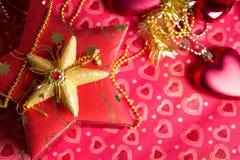 Geschenk im Kasten mit Herzdekoration am roten Hintergrund Stockfoto