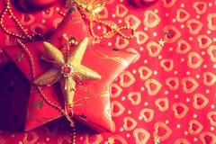 Geschenk im Kasten mit Herzdekoration am roten Hintergrund Lizenzfreies Stockfoto