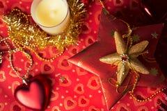 Geschenk im Kasten mit Weihnachtsdekoration am roten Hintergrund Lizenzfreie Stockfotos