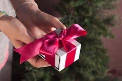 Geschenk mit rosa Band, weißer Kasten in den weiblichen Händen, Weihnachtsüberraschung, Stockfotografie