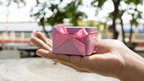 Geschenk mit rosa Band, weißer Kasten in den weiblichen Händen, Weihnachtsüberraschung, ein guten Rutsch ins Neue Jahr Stockbild