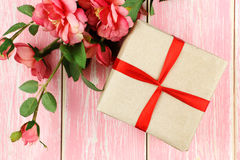 Geschenk mit rotem Band, Ring im Kasten und rosa Blumen Stockfoto