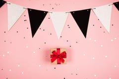 Geschenk mit rotem Bogen auf rosa Hintergrund Stockbilder