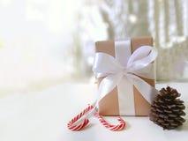 Geschenk mit weißem Bowknot, Bonbonsüßigkeiten, Kiefernkegel auf hellem Winterhintergrund lizenzfreie stockbilder