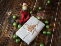 Geschenk mit Weihnachtsbällen und einem Elch Stockbild