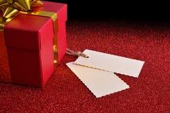 Geschenk mit zwei Tags auf der hellen roten strukturierten Tabelle erhöht Stockbilder