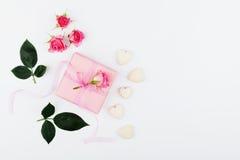 Geschenk oder Präsentkarton, Herzen und Rosarose blühen auf weißer Tischplatteansicht in Ebenenlageart für Grußkarte am Tag der F Lizenzfreie Stockfotografie