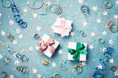 Geschenk oder Präsentkarton verzierten bunte Konfettis, Stern und Ausläufer auf blauer Weinlesetischplatteansicht flache Lageart  Stockbilder