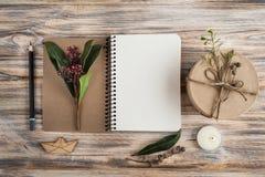Geschenk, offenes Notizbuch und Blumendekor Lizenzfreie Stockfotografie