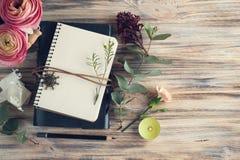 Geschenk, offenes Notizbuch und Blumendekor Stockbild