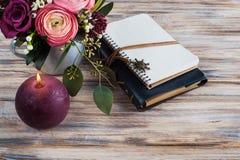 Geschenk, offenes Notizbuch und Blumendekor Stockfotografie