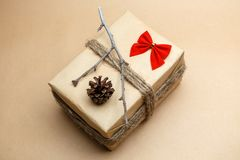 Geschenk verpackte an eco Art mit roten Blasen, pinecones und Bogen Stockfotografie