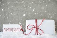 Geschenk, Zement-Hintergrund mit Schneeflocken, Adventszeit bedeutet Advent Season Stockfotos