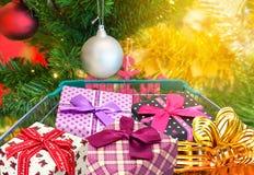 Geschenkbandgeschenkbox im Einkaufslaufkatzenwarenkorb mit Weihnachtsbaum- und Balldekorationen und unscharfen Lichtern Stockfoto