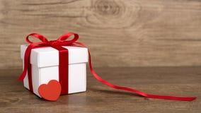 Geschenkbox auf dem hölzernen Hintergrund Rotes Farbband Rote Rose Lizenzfreie Stockbilder