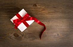 Geschenkbox auf dem hölzernen Hintergrund Rotes Farbband Rote Rose Lizenzfreies Stockfoto