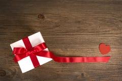 Geschenkbox auf dem hölzernen Hintergrund Rotes Farbband Rote Rose Lizenzfreie Stockfotografie