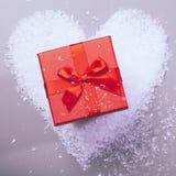 Geschenkbox auf Schneeherzen Stockfotos