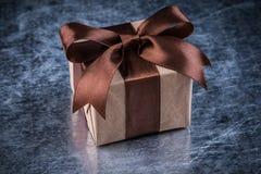 Geschenkbox auf verkratztem metallischem Hintergrundfeiertagskonzept Lizenzfreie Stockfotos