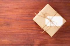 Geschenkbox in das braune Papier gebunden durch Schnur mit leerer weißer Karte auf altem Holztisch mit Raum für Text Stockfotos