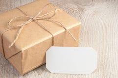 Geschenkbox in das braune Papier gebunden durch Schnur mit leerer weißer Karte auf weißem Holztisch mit Raum für Text Lizenzfreie Stockfotos