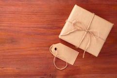 Geschenkbox in das braune Papier gebunden durch Schnur und leeres Tag auf altem Holztisch mit Raum für Text Lizenzfreies Stockbild