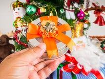 Geschenkbox in der Hand auf Weihnachtsbaumhintergrund Stockfotos