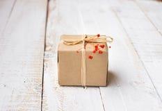 Geschenkbox eingewickelt im Kraftpapier gebunden mit Schnur, zarte kleine rote Blume Lizenzfreie Stockbilder