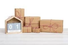 Geschenkbox eingewickelt im Recyclingpapier mit Bandbogen und im Kalender am 1. Januar auf Holztisch Getrennt Lizenzfreies Stockfoto