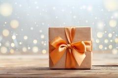 Geschenkbox eingewickelt mit Kraftpapier und Bogen auf neutralem Hintergrund mit boke Glücklicher Mann genießt an den Feiertagen  lizenzfreie stockfotos