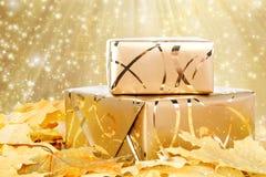Geschenkbox im Goldpackpapier mit Herbstlaub Lizenzfreies Stockfoto