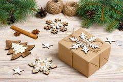 Geschenkbox im Kraftpapier mit Weihnachtsdekoration, Schnurseil, Konzepthintergrund, Draufsicht über hölzerne Tischplatte Weihnac Lizenzfreies Stockfoto