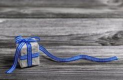 Geschenkbox mit Blau überprüfte Band auf hölzernem grauem Hintergrund Stockfotos