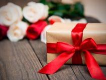 Geschenkbox mit blured roten und weißen Rosen auf einem dunklen hölzernen backgr Lizenzfreie Stockfotografie