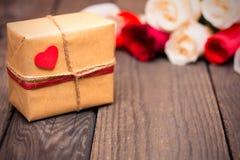 Geschenkbox mit blured roten und weißen Rosen auf einem dunklen hölzernen backgr Lizenzfreies Stockbild