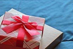 Geschenkbox mit Bogen auf Betthintergrund Stockfotografie