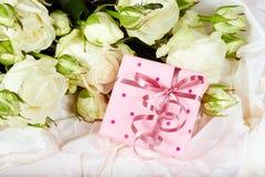 Geschenkbox mit Bogen- und Weißrosenblumen Stockfotos