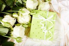 Geschenkbox mit Bogen- und Weißrosenblumen Stockfotografie