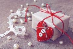 Geschenkbox mit einem Band, einem roten Herzen und Perlen auf Segeltuch backgroun Stockfotos