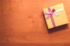 Geschenkbox mit einem Bogen auf Holztisch instagram Filter Stockfotos