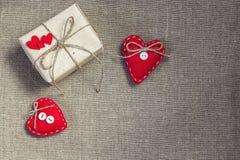 Geschenkbox mit einem natürlichen Seil und zwei rote Herzen auf dem Rausschmiß Lizenzfreie Stockbilder
