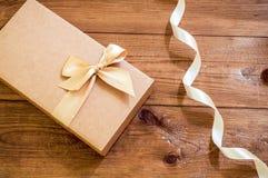 Geschenkbox mit Goldbogen auf hölzernem Hintergrund lizenzfreie stockbilder