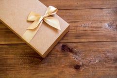 Geschenkbox mit Goldbogen auf hölzernem Hintergrund lizenzfreie stockfotografie