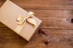 Geschenkbox mit Goldbogen auf hölzernem Hintergrund stockbild