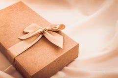 Geschenkbox mit Goldbogen auf weißem Stoffhintergrund stockfotos