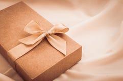 Geschenkbox mit Goldbogen auf weißem Stoffhintergrund lizenzfreies stockbild